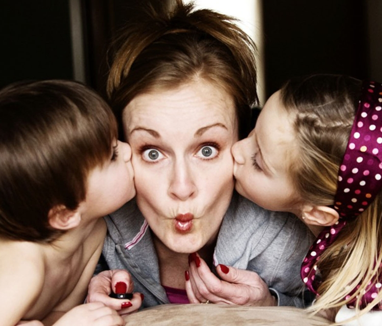 Mom-with-puckered-lips-kissed-by-kids